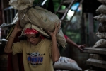 A young man carrying a sack full of stones from a tunnel in Diwalwal. Depending on their size, they can weigh 50-80 kilograms.